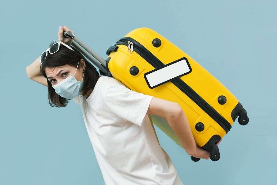 Ragazza porta sulle spalle una valigia