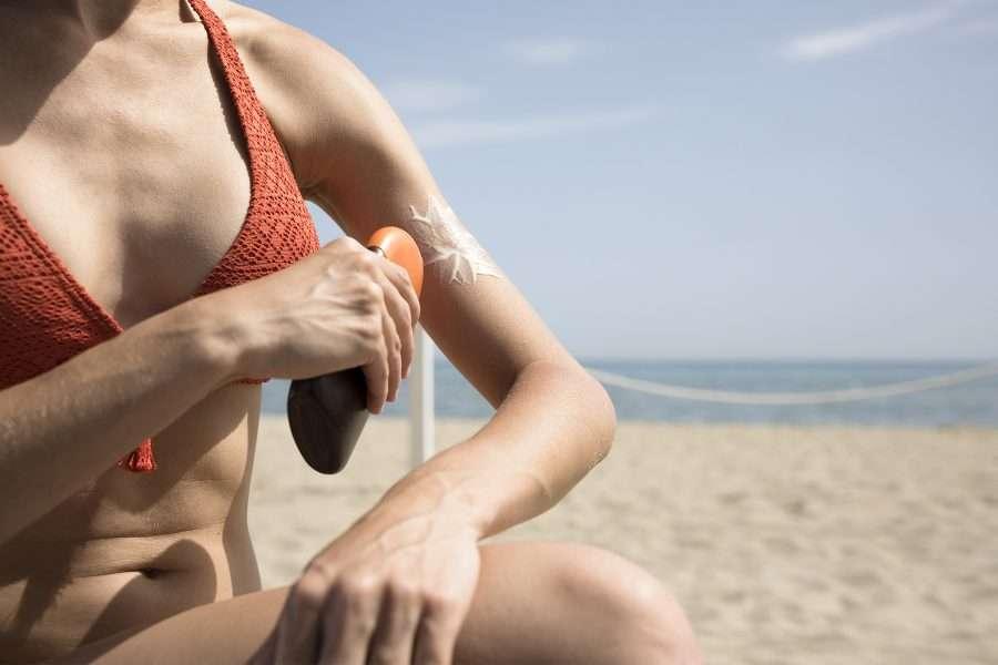 Donna in spiaggia applica una crema solare