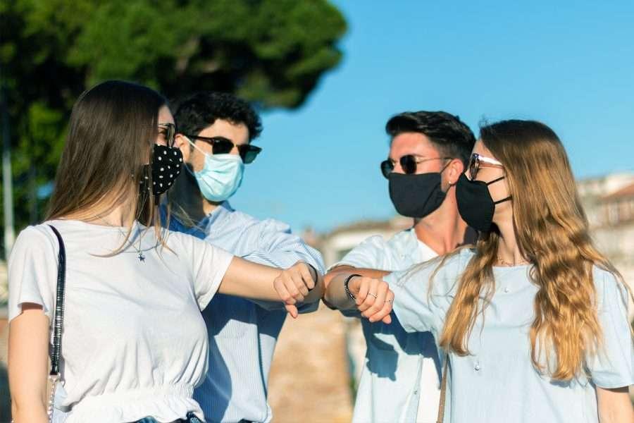 Gruppo di ragazzi si riunisce nel rispetto delle misure di sicurezza e con i dispositivi di protezione individuale imposti contro Covid-19