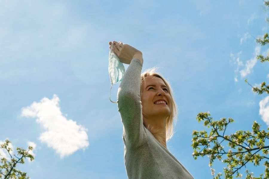 Donna che sorride guardando il cielo con una mascherina in mano